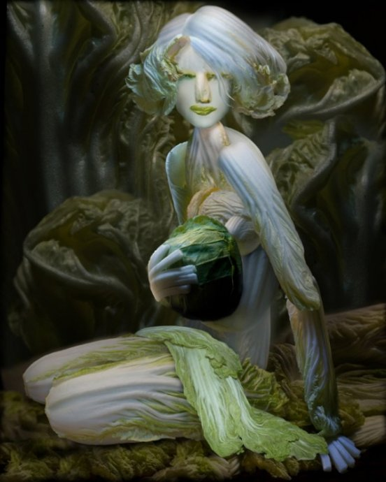 A sculpture of a reclining woman made from cabbage.